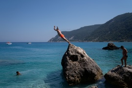 A man dives at Agios Nikitas beach in Greece [File: Dimitris Rapakousis/Reuters]