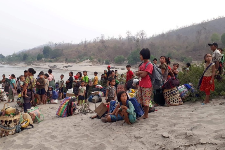 Karen refugees carrying belongings are seen at Salween riverbank in Mae Hong Son, Thailand on March 29, 2021 [Karen Women's Organization/Handout via Reuters]