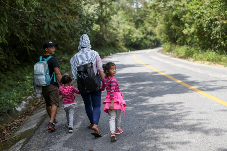 A Honduran migrant family walking on a highway on the outskirts of Palenque, Mexico [Edgard Garrido/Reuters]