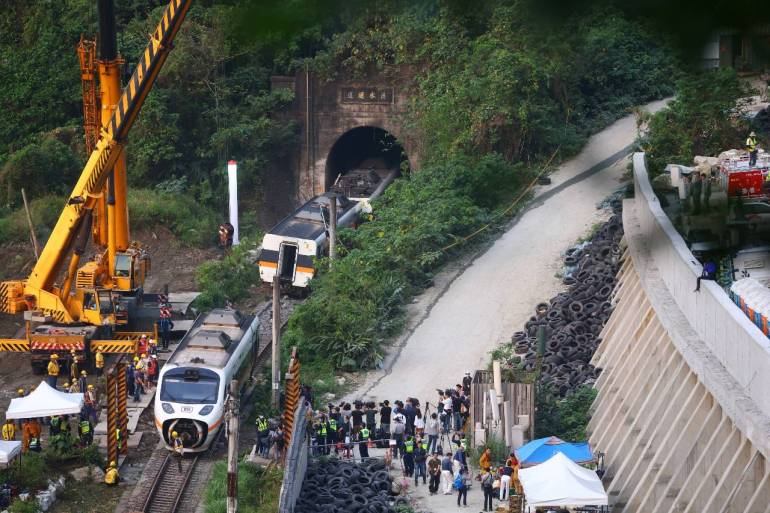 Rescuers work at the site a day after Friday's deadly train derailment at a tunnel north of Hualien [Ann Wang/Reuters]