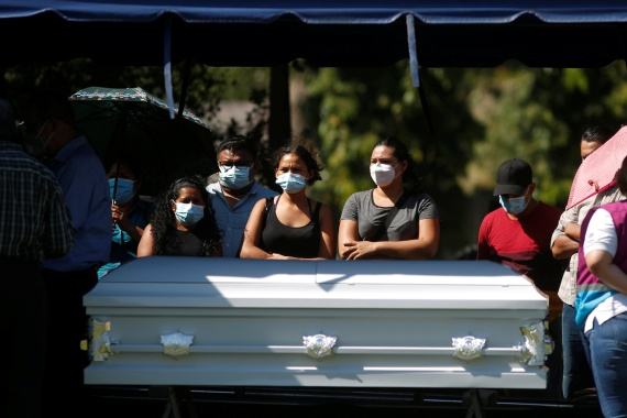Relatives stand by the coffin that contains the body of Victoria Salazar, a Salvadoran woman who died after a Mexican police officer was seen kneeling on her back in a video, at a cemetery during her burial in Sonsonate, El Salvador on April 4, 2021 [Jose Cabezas/ Reuters]
