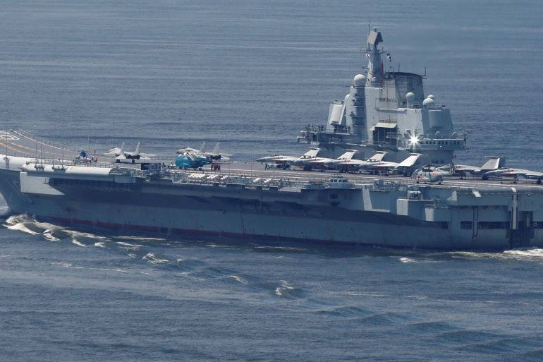 China's navy said the carrier group, lead by the Liaoning, the country's first aircraft carrier put into active service, was carrying out 'routine' drills in the waters near Taiwan [File: Bobby Yip/Reuters]