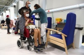 A woman in a wheelchair receives the vaccine at Enfermera Isabel Zendal hospital in Madrid, Spain, [Sergio Perez/REUTERS]