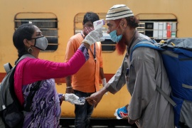 A health worker checks a passenger's temperature and pulse at a railway station platform in Mumbai, India [Francis Mascarenhas/Reuters]
