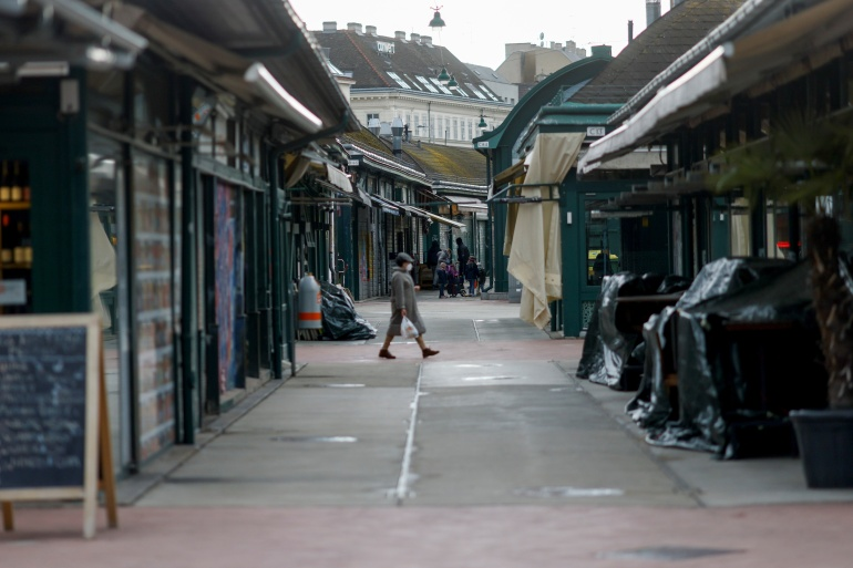 A person passes closed restaurants and shops at a market after the local government extended the lockdown due to the COVID-19 outbreak in Vienna, Austria [Leonhard Foeger/Reuters]