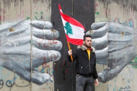 A man holds a Lebanese flag as demonstrators gather during a protest over the deteriorating economic situation, in Beirut, Lebanon April 10, 2021. (Aziz Taher/Reuters)