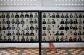 A visitor looks at pictures of victims of the Khmer Rouge regime at the notorious Tuol Sleng former prison [File: Damir Sagol/Reuters]
