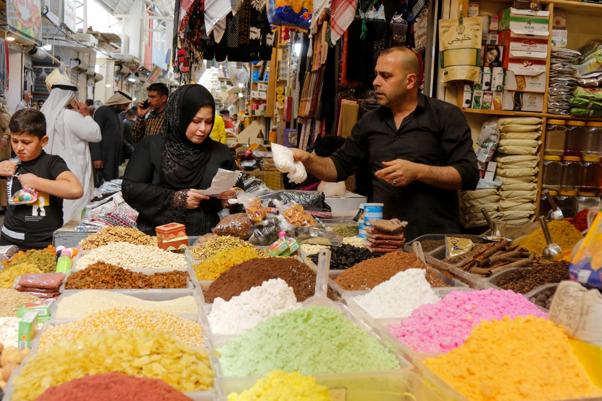 An Iraqi woman shops at a wholesale market ahead of the holy fasting month of Ramadan, in Mosul, Iraq. [Khalid Al-Mousily/Reuters]