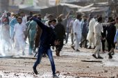 A supporter of the Tehreek-e-Labaik Pakistan (TLP) party hurls stones towards police (not in picture) during a protest against the arrest of their leader in Lahore, Pakistan April 13, 2021 [Reuters]