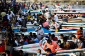 Migrant people and workers leave Dhaka in speedboats before the countrywide lockdown, at Mawa ferry port in Munshiganj [Mohammad Ponir Hossain/Reuters]
