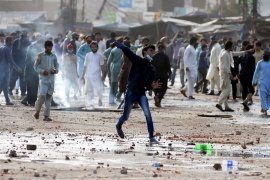 A supporter of the Tehreek-e-Labaik Pakistan (TLP) party hurls stones towards police (not pictured) during a protest [File: Reuters]