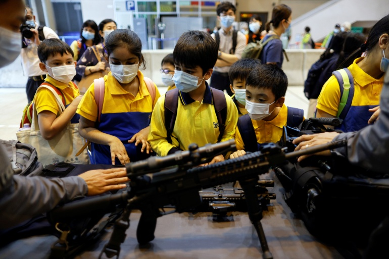 Children look at a submachine gun during an open day to mark the National Security Education Day, at Hong Kong Police College, in Hong Kong, China April 15, 2021 [Tyrone Siu/ Reuters]