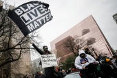 Alex Harder waves a Black Lives Matter flag during a march through downtown after the closing statements in the trial of former police officer Derek Chauvin, who is facing murder charges in the death of George Floyd, in Minneapolis, Minnesota, US, April 19, 2021. [Nicholas Pfosi/Reuters]