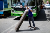 A man carries a filled oxygen cylinder to load into a truck for a hospital outside a private refilling station in New Delhi [Adnan Abidi/Reuters]