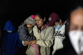 Migrant families pray after crossing the Rio Grande into the United States from Mexico, in Roma, Texas, on April 20 [Go Nakamura/Reuters]