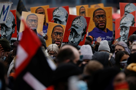 People hold placards after the verdict in the trial of former Minneapolis police officer Derek Chauvin, in front of Hennepin County Government Center, in Minneapolis, Minnesota, April 20, 2021 [Carlos Barria/Reuters]