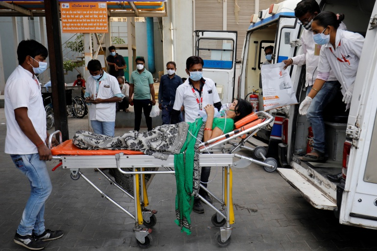 A patient wearing an oxygen mask is wheeled inside a COVID-19 hospital for treatment, amid the spread of the coronavirus disease (COVID-19) in Ahmedabad, India, April 21, 2021 [Amit Dave/REUTERS]