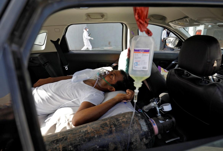 Pasıent s problemamı dyhanııa v avtomobıle, ojıdaıýshıı postýplenııa v bolnısý s COVID-19 dlıa lechenııa v Ahmedabade.  [Amıt Deıv / Reıter]