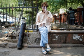 A patient, wearing an oxygen mask, sits outside Lok Nayak Jai Prakash Narayan Hospital, one of India's largest facilities for coronavirus disease patients only [Reuters]