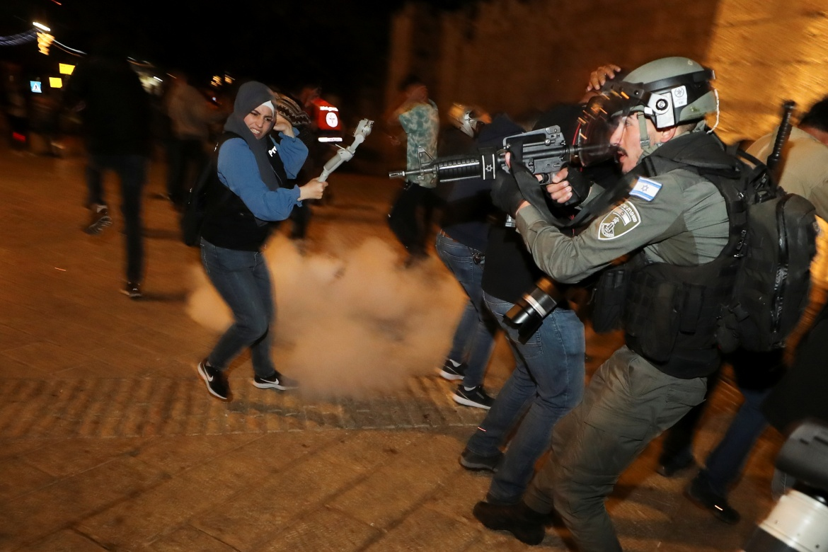 Israeli police stand in position as a stun grenade explodes by the gate to Jerusalem's Old City. [Ammar Awad/Reuters]