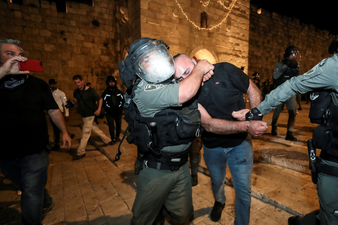 Israeli police detain a Palestinian in Jerusalem's Old City. There have been nightly disturbances since the start of the Muslim holy month of Ramadan on April 13, amid Palestinian anger over police blocking off access to the promenade around the walls of the Old City and a ban on gatherings. [Ammar Awad/Reuters]
