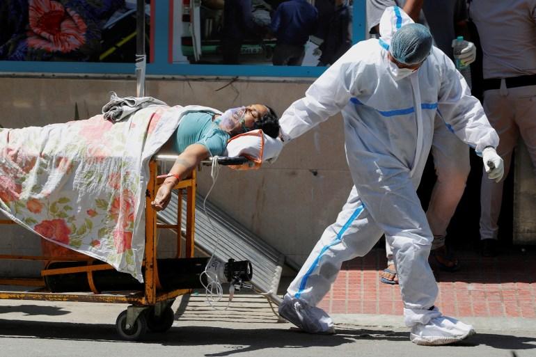 Seorang petugas kesehatan membawa pasien yang menderita virus corona di luar bangsal korban di rumah sakit Guru Teg Bahadur, di New Delhi, India [Adnan Abidi / REUTERS]