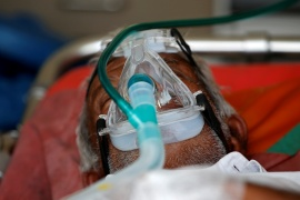 A patient wearing an oxygen mask is seen inside an ambulance waiting to enter a COVID-19 hospital for treatment in Ahmedabad [File: Amit Dave/Reuters]