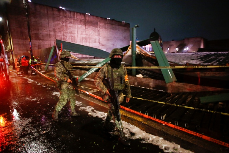 "Soldiers walk by a scene where the roof protecting the ""Casa de las Aguilas"", part of the ruins of the Templo Mayor archaeological site, collapsed after heavy rain and hail, in downtown Mexico City, Mexico [Gustavo Graf/Reuters]"