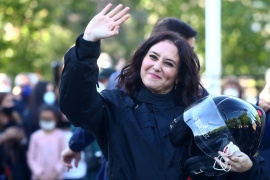 Madrid regional government leader Isabel Diaz Ayuso waves to supporters upon arriving by motorbike to an electoral event [File: Sergio Perez/Reuters]