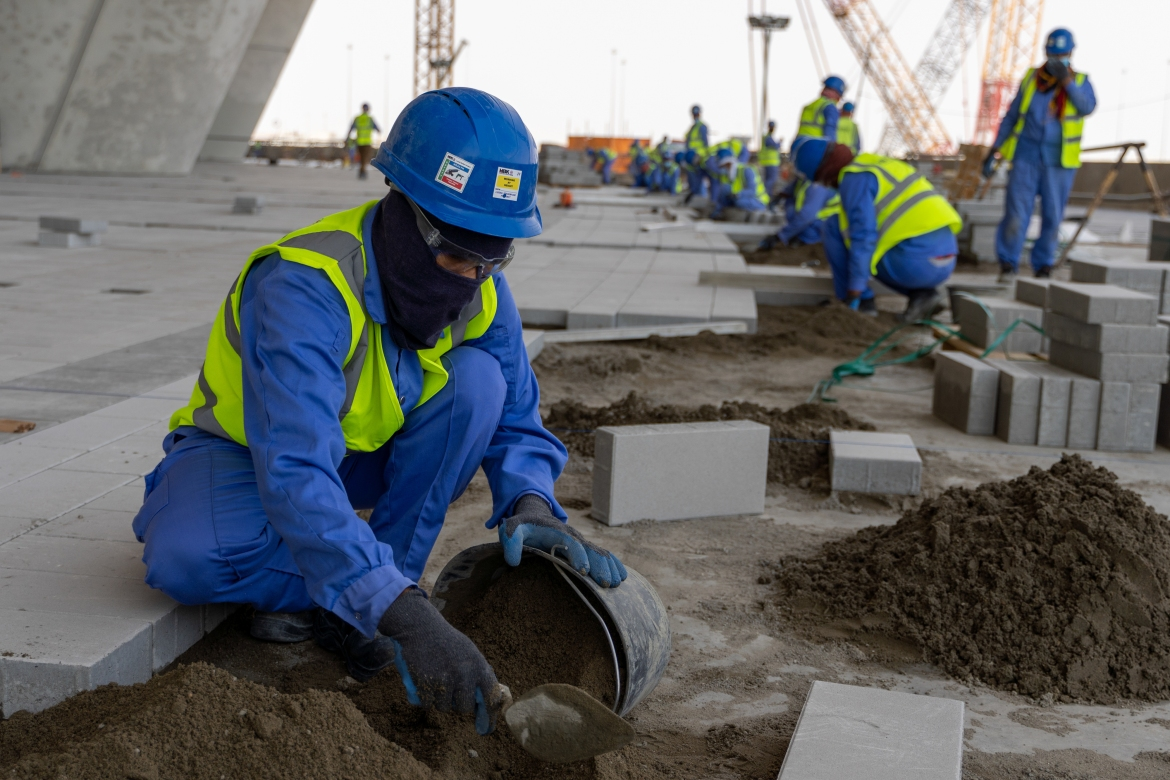 """Qatar's treatment of its migrant workers has been under the spotlight ever since it was awarded hosting rights in 2010. Tournament organisers have said: """"Compliance with ... all relevant Qatari laws will be a prerequisite to the selection and retention by the SC of its contractors and sub-contractors."""" [Sorin Furcoi/Al Jazeera]"""