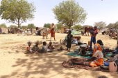 Refugees fleeing recent violence in Sudan's Darfur region sit in shade near the town of Adre, Chad. [Courtesy: UNHCR]
