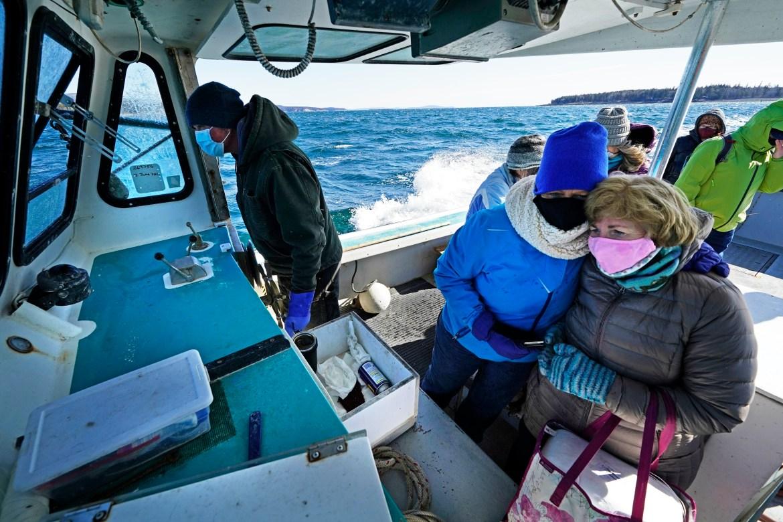 Perawat Kathy Cheney dan Maureen Giffen berkerumun dalam perjalanan basah dan berangin di atas kapal lobster dalam perjalanan untuk mendirikan klinik vaksinasi COVID-19 di Great Cranberry Island, Maine, Amerika Serikat.  [Robert F Bukaty / Foto AP]