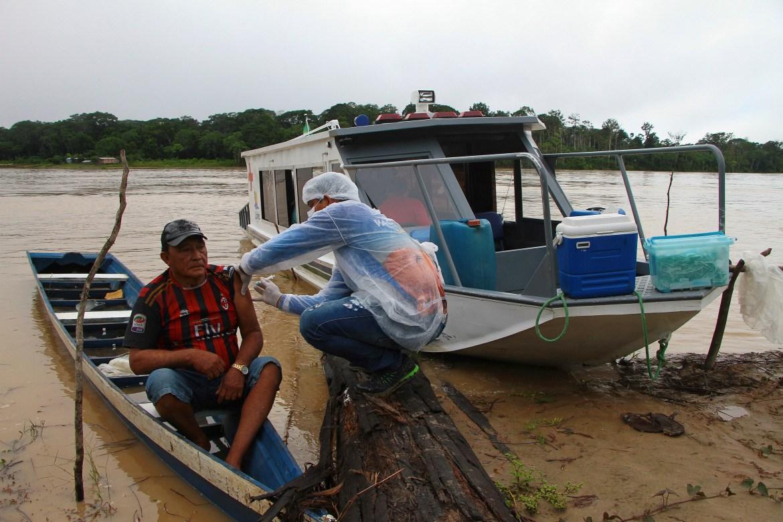 Luis Alves Nogueira, 74, kiri, menerima satu dosis vaksin Oxford-AstraZeneca dari petugas kesehatan, di komunitas Pupuri di sepanjang Sungai Purus, di kotamadya Labrea, negara bagian Amazonas, Brasil.  [Foto Edmar Barros / AP]
