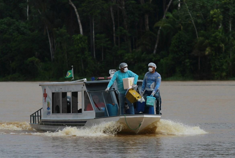 Petugas kesehatan Diego Feitosa Ferreira, 28, kanan, dan Clemilton Lopes de Oliveira, 41, melakukan perjalanan dengan perahu ke komunitas Santa Rosa, negara bagian Amazonas, Brasil.  [Foto Edmar Barros / AP]