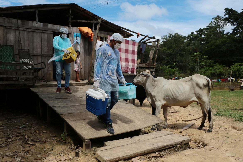 Petugas kesehatan Diego Feitosa Ferreira, 28, kanan, dan Clemilton Lopes de Oliveira, 41, meninggalkan rumah setelah seorang penduduk menolak untuk divaksinasi terhadap virus corona baru, di komunitas Capacini, di sepanjang Sungai Purus, di kotamadya Labrea, negara bagian Amazonas , Brazil.  [Foto Edmar Barros / AP]