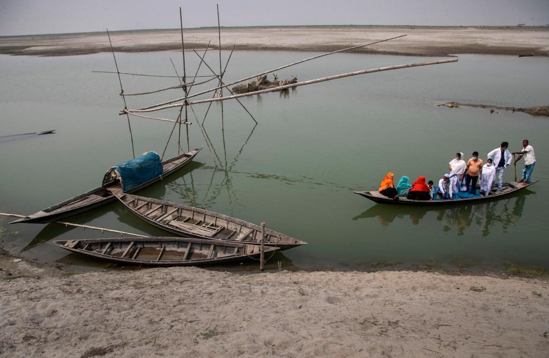 Petugas kesehatan menemani penduduk desa lanjut usia dengan perahu saat mereka menyeberangi Sungai Brahmaputra untuk mencapai pusat vaksinasi COVID-19 di desa Bahakajari di negara bagian Assam di timur laut India.  [Foto Anupam Nath / AP]