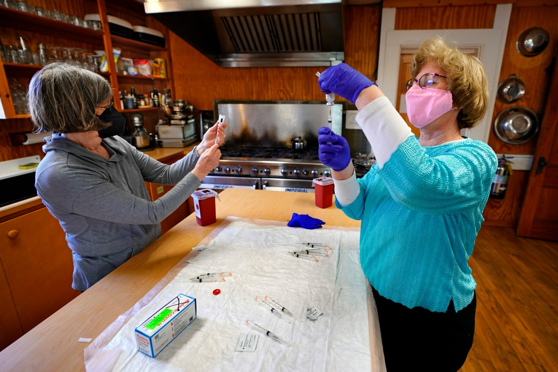 Perawat Sharon Daley, kiri, dan Maureen Giffen mengisi jarum suntik dengan vaksin Moderna di klinik darurat di dapur pusat komunitas di Great Cranberry Island, Maine.  [Robert F Bukaty / Foto AP]