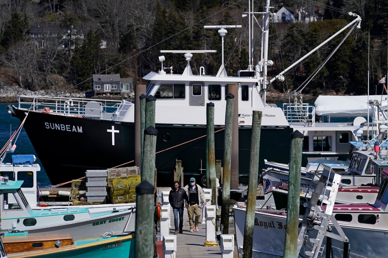 Marc Nighman dan Jonathan Partin meninggalkan Sunbeam setelah menerima vaksin COVID-19, di Northeast Harbor, Maine.  Kapal setinggi 74 kaki yang dioperasikan oleh nirlaba Maine Seacoast Mission, terlihat di latar belakang, telah memvaksinasi ratusan penduduk pulau.  [Robert F Bukaty / Foto AP]