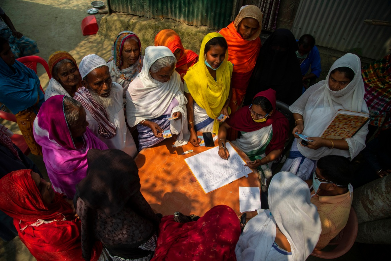 Wanita lansia menunggu untuk mendaftar vaksin COVID-19 di desa Bahakajari di negara bagian Assam di timur laut India.  Di India, para pekerja baru-baru ini berjalan kaki ke desa kecil itu untuk mulai memvaksinasi hampir 9.000 penduduknya.  [Foto Anupam Nath / AP]