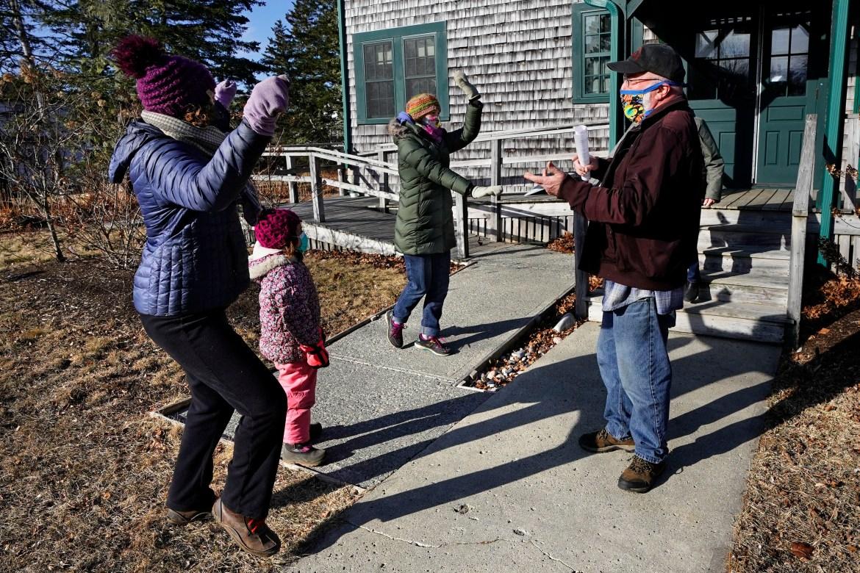 Penduduk pulau, Lindsay Eysnogle, kiri, putrinya, Marina Pickering dan Kaitlyn Miller, tengah, menari gembira bersama Mitchell McCormick untuk merayakan vaksinasi COVID-19 mereka di Islesford, Maine, Amerika Serikat.  [Robert F Bukaty / Foto AP]