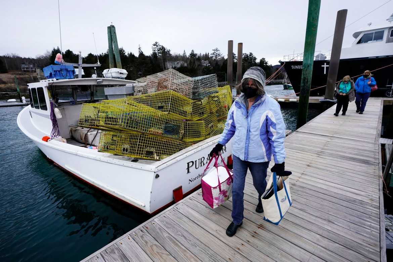 Perawat Sharon Daley membawa pendingin vaksinasi COVID-19 saat dia dan stafnya memulai perjalanan untuk menyuntik penduduk pulau di Northeast Harbor, Maine, Amerika Serikat.  [Robert F Bukaty / Foto AP]