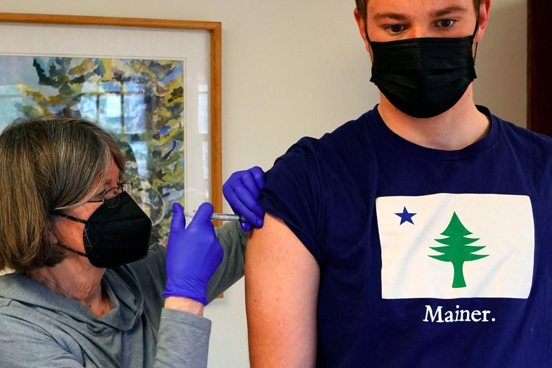 Perawat Sharon Daley memberikan vaksinasi COVID-19 kepada Oliver Blank, 18, di pulau Islesford, Maine, Amerika Serikat.  Pengecualian telah dibuat untuk pembatasan usia vaksinasi untuk memungkinkan penduduk yang lebih muda di pulau-pulau terpencil untuk menerima suntikan mereka.  [Robert F Bukaty / Foto AP]