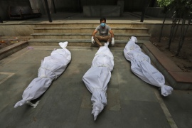 A man waits for the cremation of a relative who died of COVID-19, placed near bodies of other victims, in New Delhi. [AP Photo]