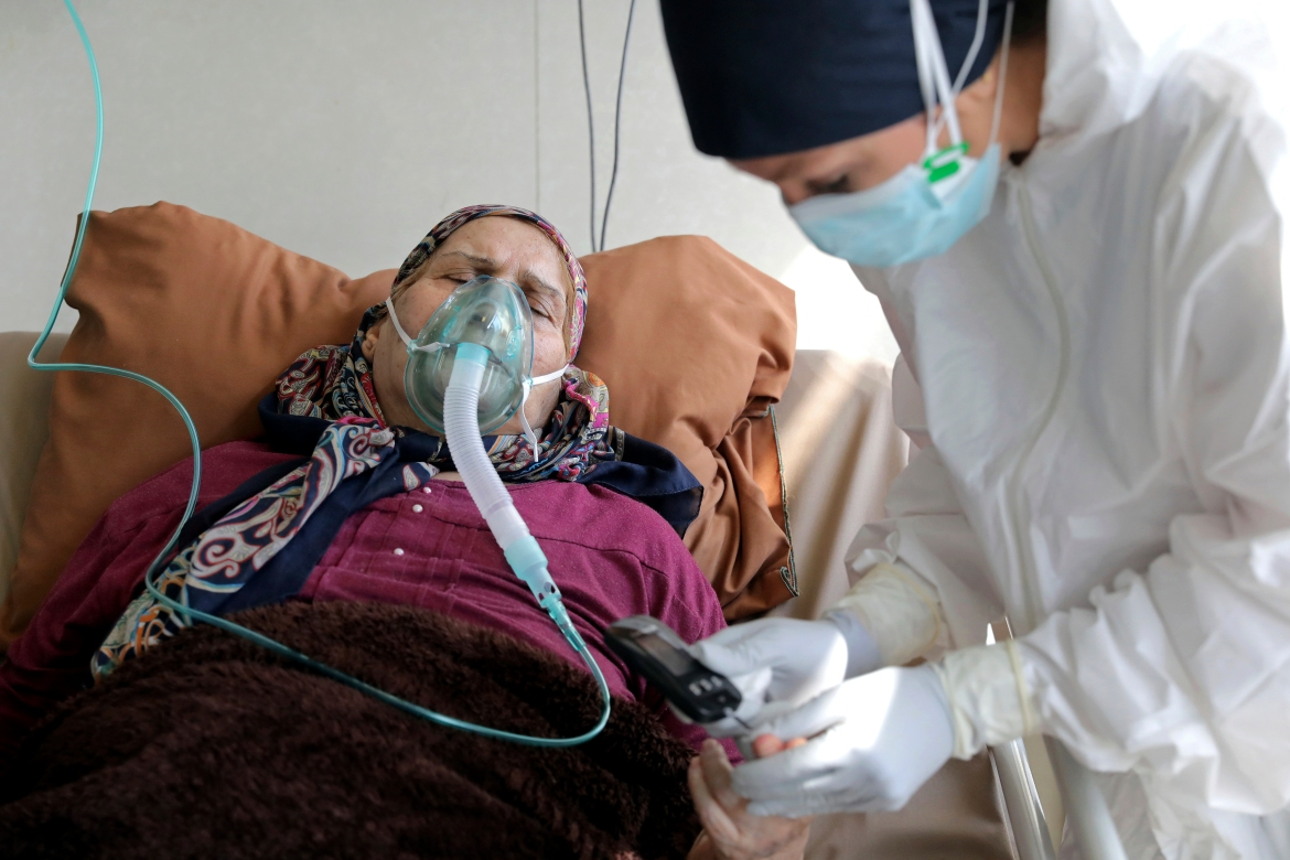 A nurse tends to a patient infected by COVID-19 at the Shohadaye Tajrish Hospital in Tehran. [Ebrahim Noroozi/AP Photo]