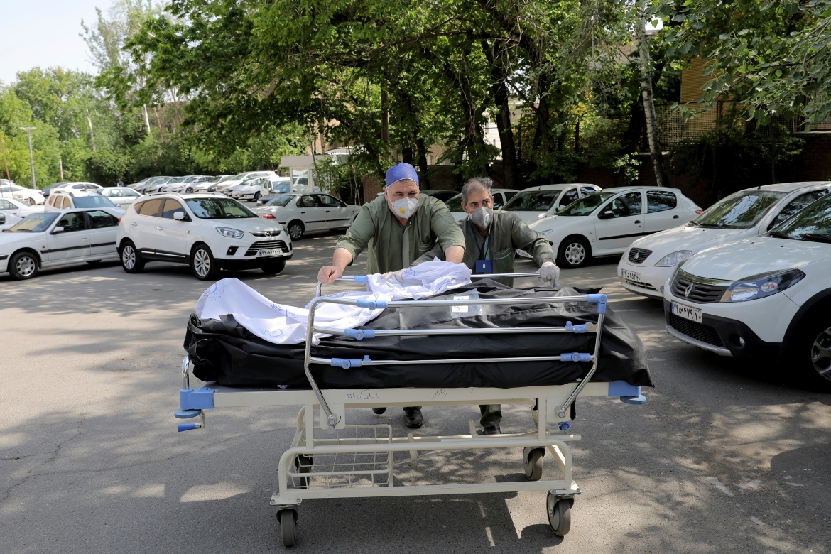 Hospital workers move bodies of patients who died from COVID-19 at  Shohadaye Tajrish Hospital in Tehran. [Ebrahim Noroozi/AP Photo]
