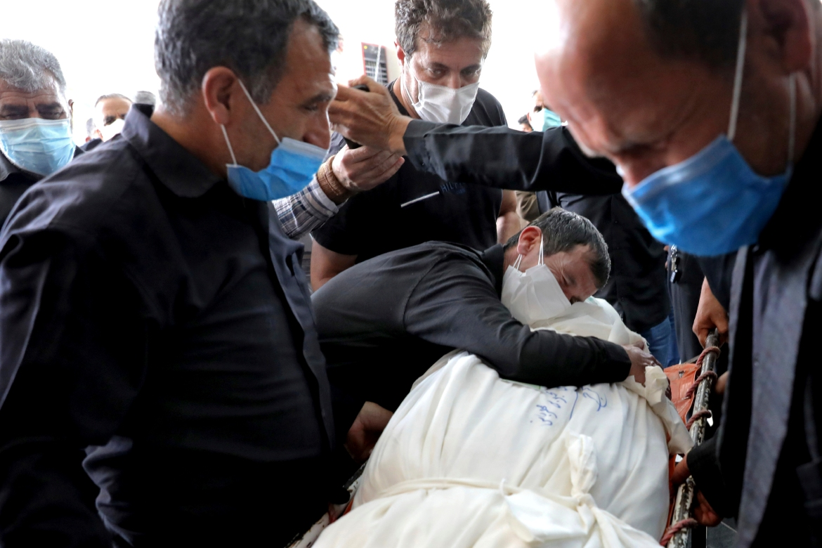 A relative hugs the body of a person who died from COVID-19 at the Behesht-e-Zahra cemetery. [Ebrahim Noroozi/AP Photo]