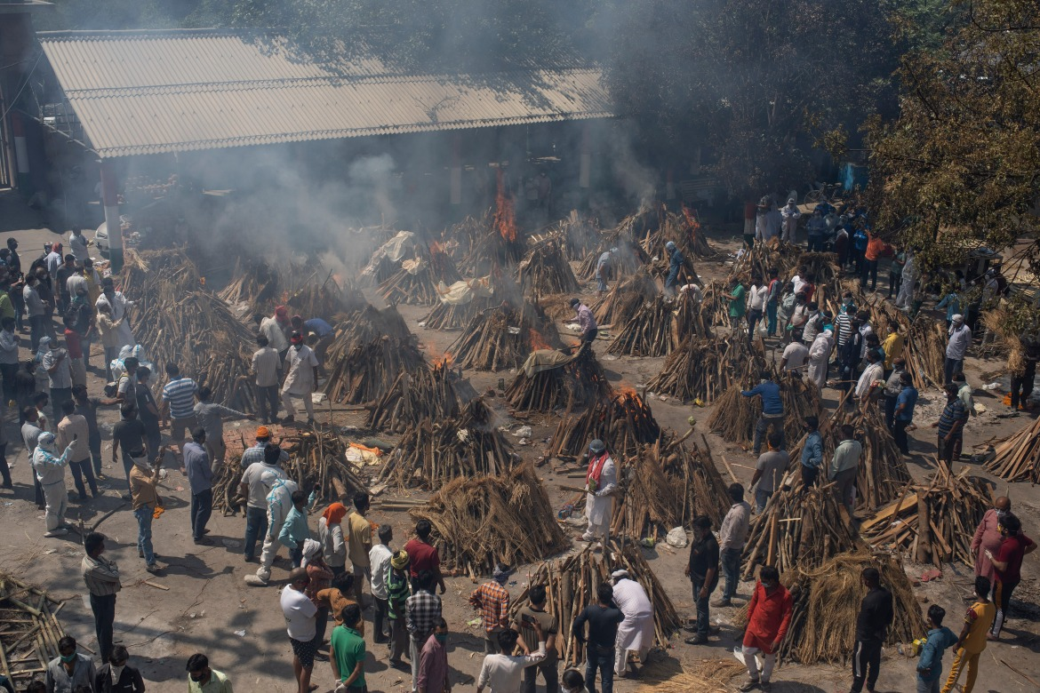 Multiple funeral pyres of those who died of COVID-19 burn at a ground that has been converted into a crematorium for mass cremation of coronavirus victims in New Delhi. [Altaf Qadri/AP Photo]