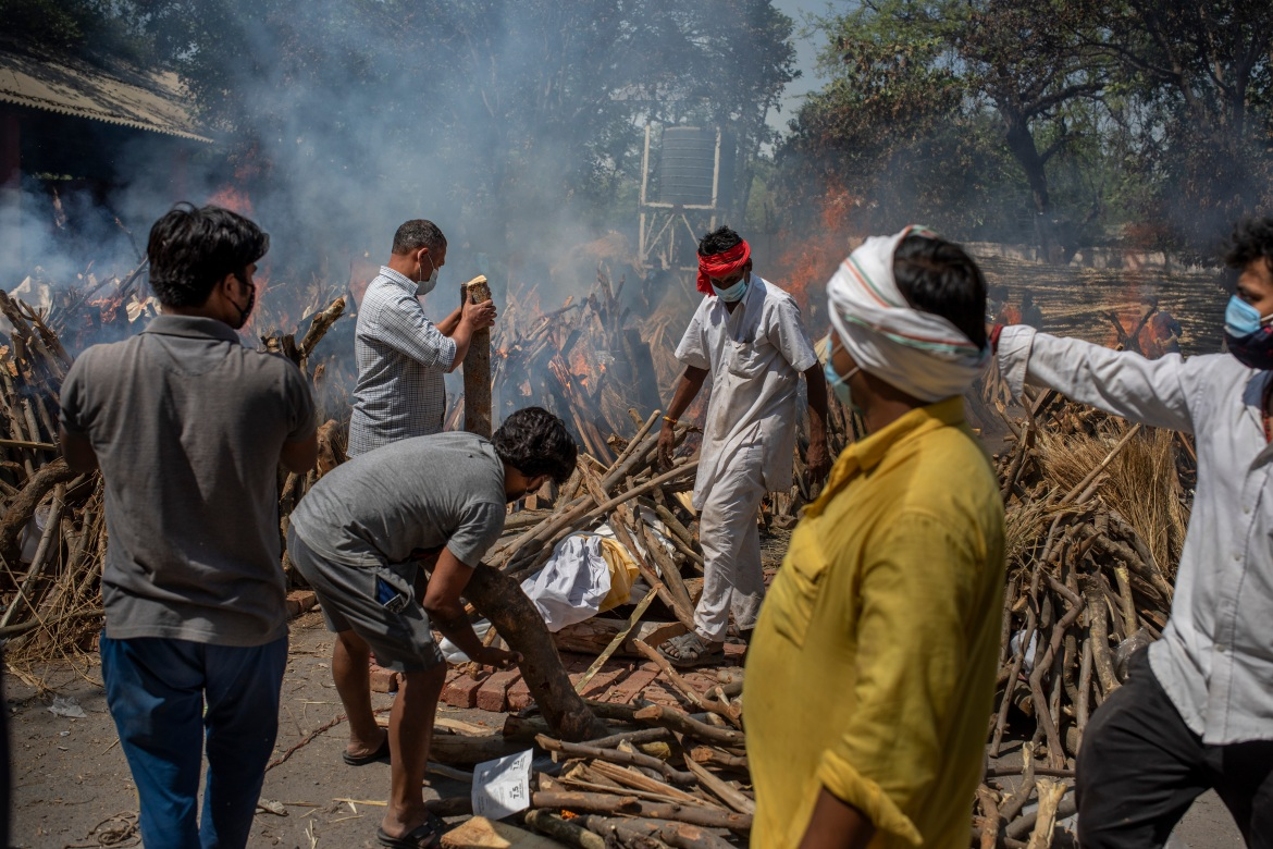 Members of a family of COVID-19 victim prepare a funeral pyre as multiple pyres are seen at a crematorium in New Delhi. [Altaf Qadri/AP Photo]