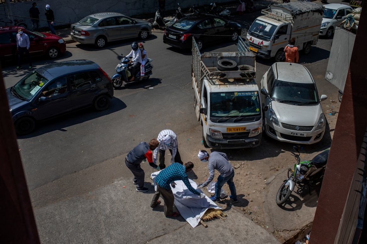 Members of the family of a COVID-19 victim put a shroud over the body lying on a road outside a crematorium in New Delhi. [Altaf Qadri/AP Photo]