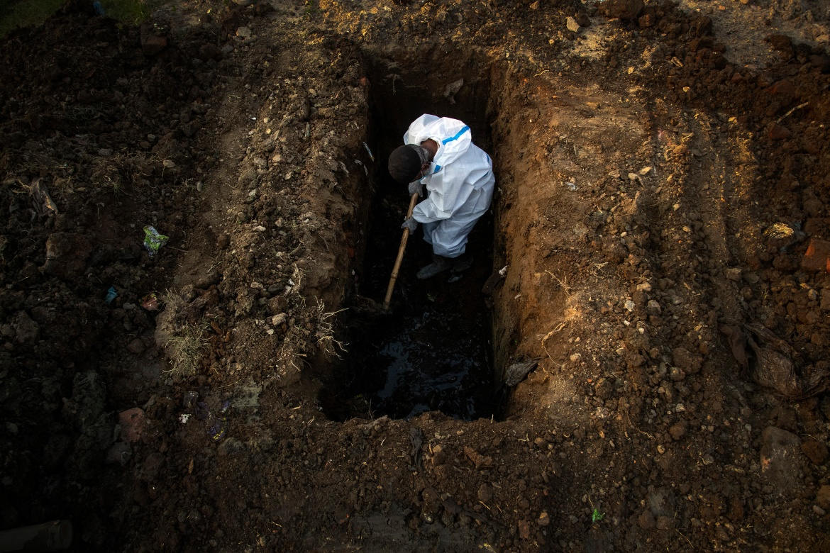 A man in a protective suit digs a grave for the body of a person who died of COVID-19 in the northeastern city of Guwahati. [Anupam Nath/AP Photo]